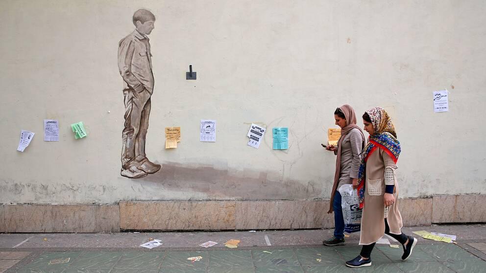 Två kvinnor går på gatan i Irans huvudstad Teheran.