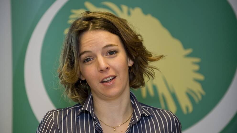 Bild på Zaida Catalán med miljöpartiets logotyp i bakgrunden.