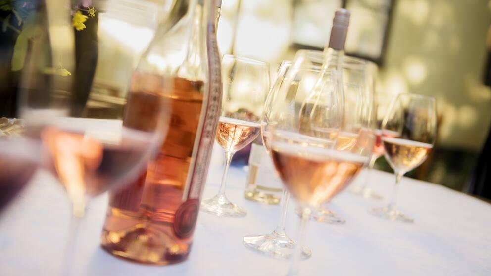 Två flaskor rosévin och halvfulla glas framdukade på ett vit bord