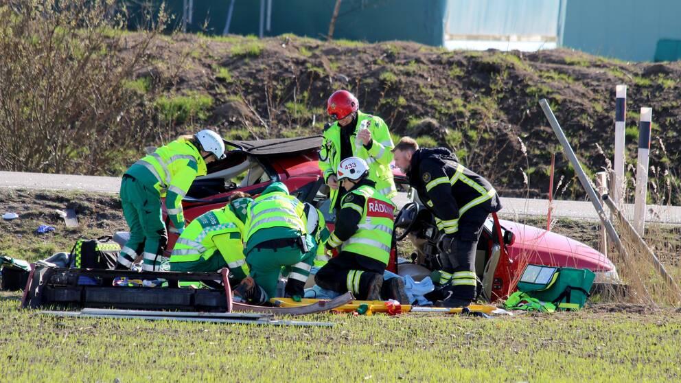 räddningstjänstpersonal framför bil i diket