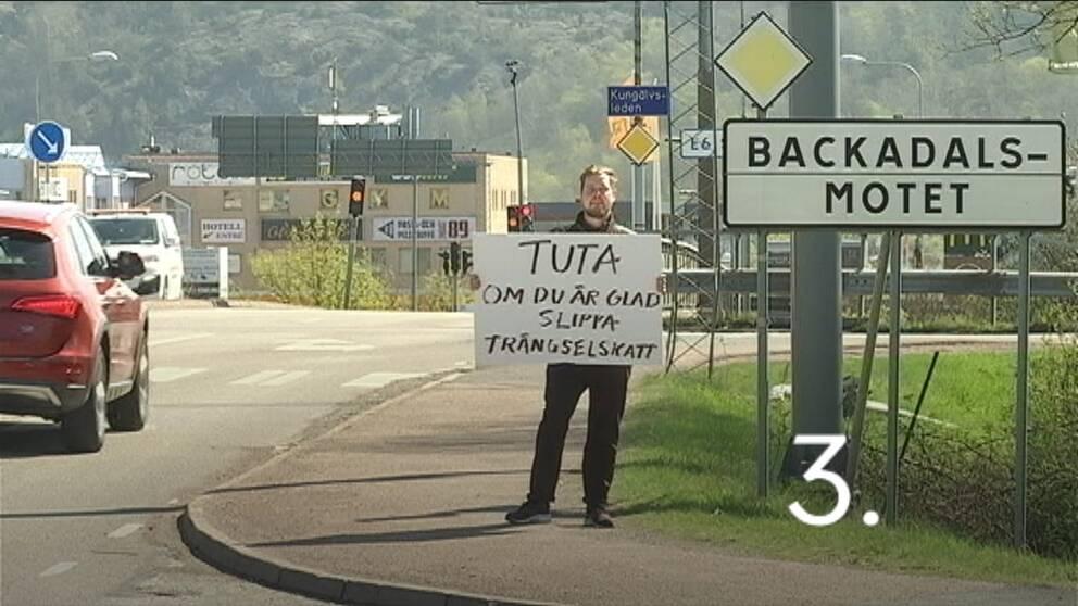 """Reportern står i vägkorsning bredvid vägskylt """"Backadalsmotet"""" med handskrivet plakat: """"Tuta om du är glad att slippa trängselskatt"""""""