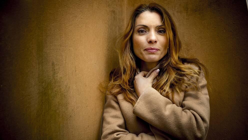 Författaren och journalisten Alexandra Pascalidou framför en sandigt, varm gul vägg utomhus.