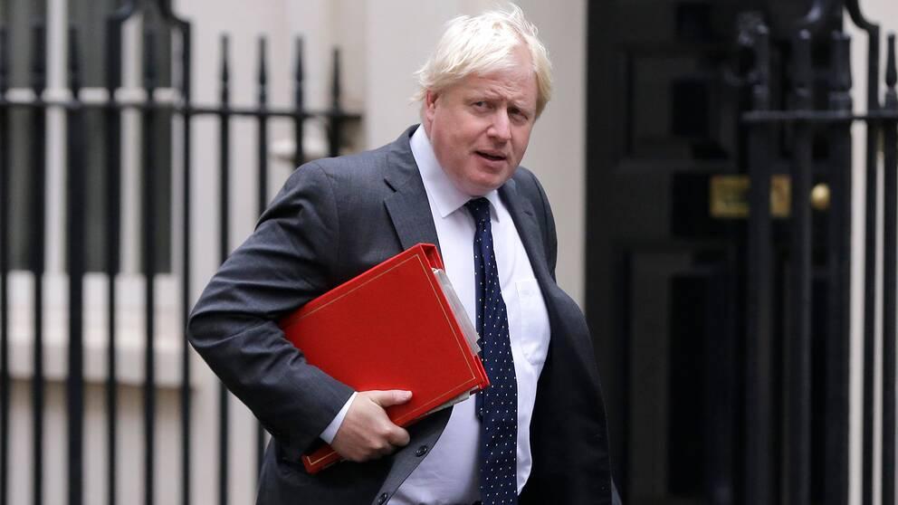Storbritanniens utrikesminister Boris Johnson gåendes med en röd pärm under armen.