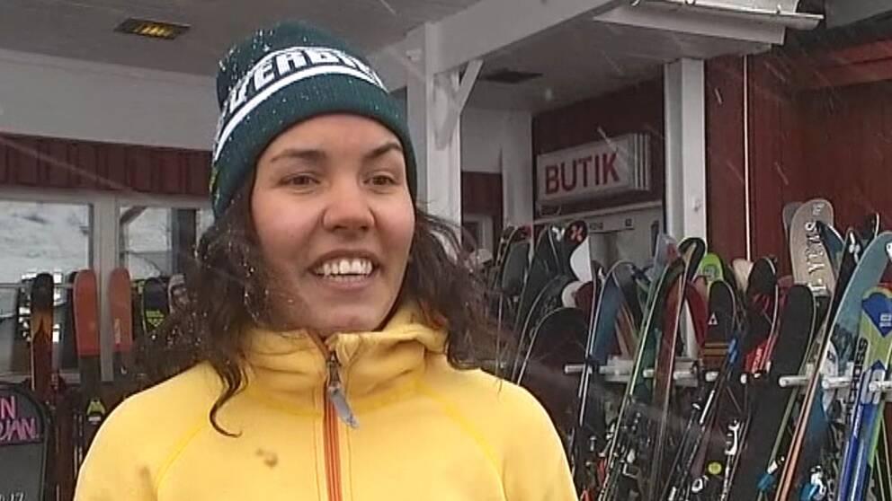 leende tjej i snöblåst, skidställ i bakgrund