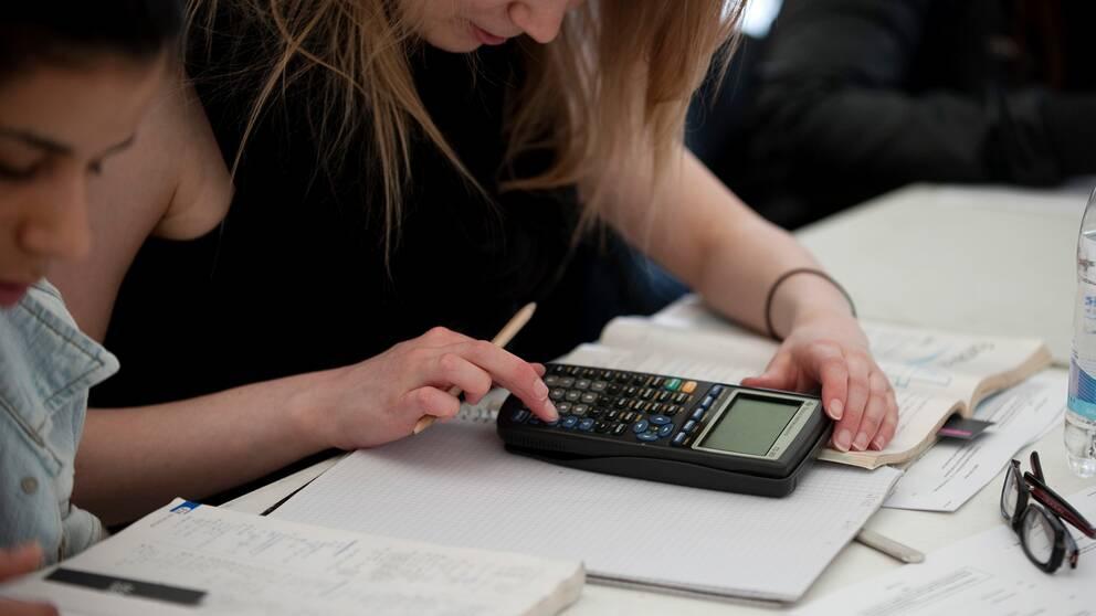 En elev löser matteuppgifter och slår in på en miniräknare.