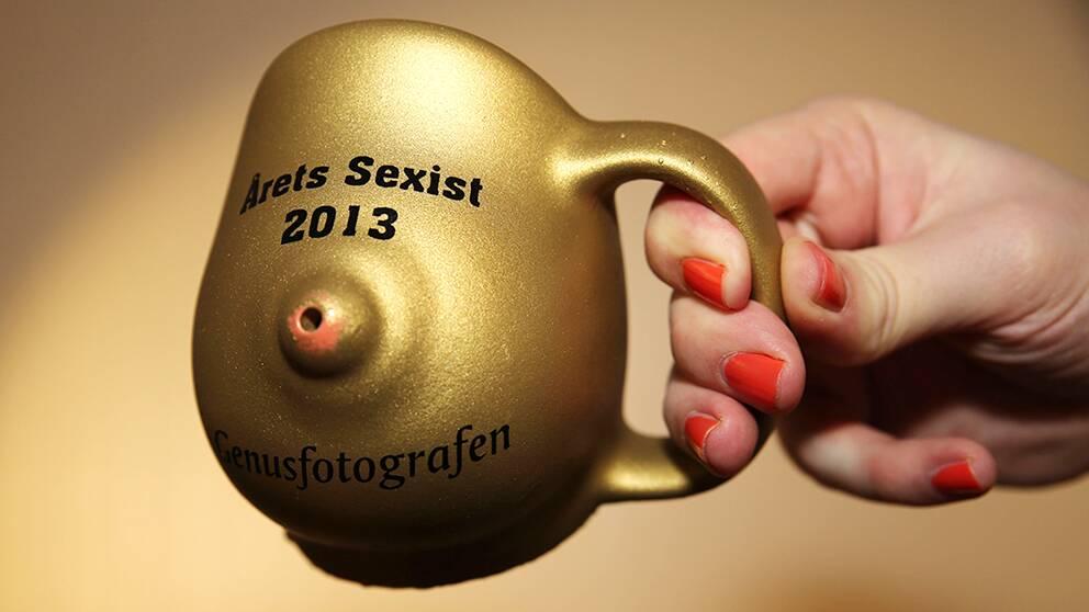 """Priset är en guldig mugg föreställandes ett bröst med texten """"Årets sexist 2013"""" på."""