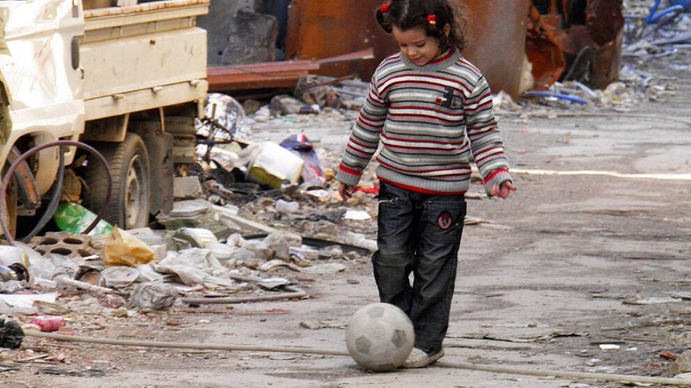 En flicka leker med en fotboll på en av de sönderbombade gatorna i centrala Homs.