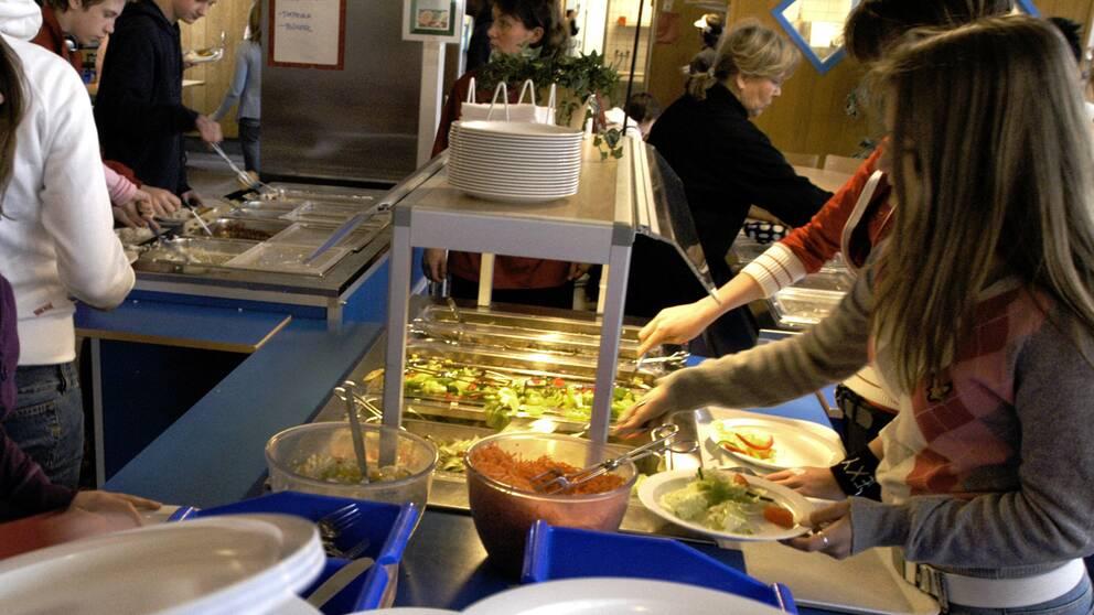 Elever tar mat i skolmatsalen.