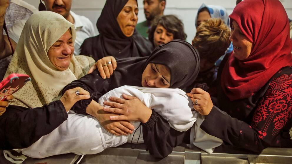 Ett spädbarn är inlindat i vitt tyg och ska begravas, tre kvinnor håller om det och gråter.