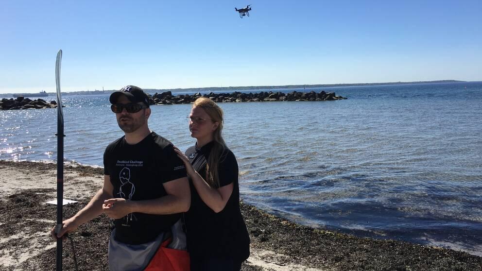 Dövblinde Torbjörn Svensson på stranden tillsammans med en kvinnlig tolk.