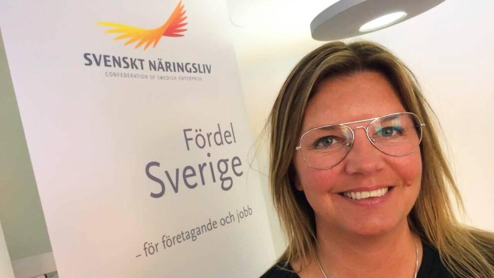 På bilden syns en kvinna med glasögon. Bakom henne finns en skärm som det står Svenskt Näringsliv på.