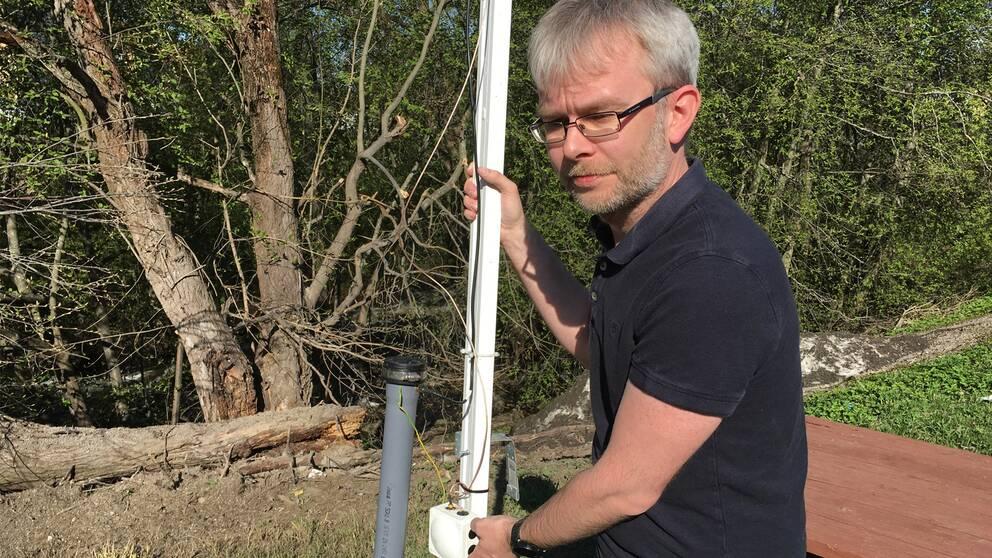 Forskaren Rikard Hamrin håller mätinstrumentet utomhus.