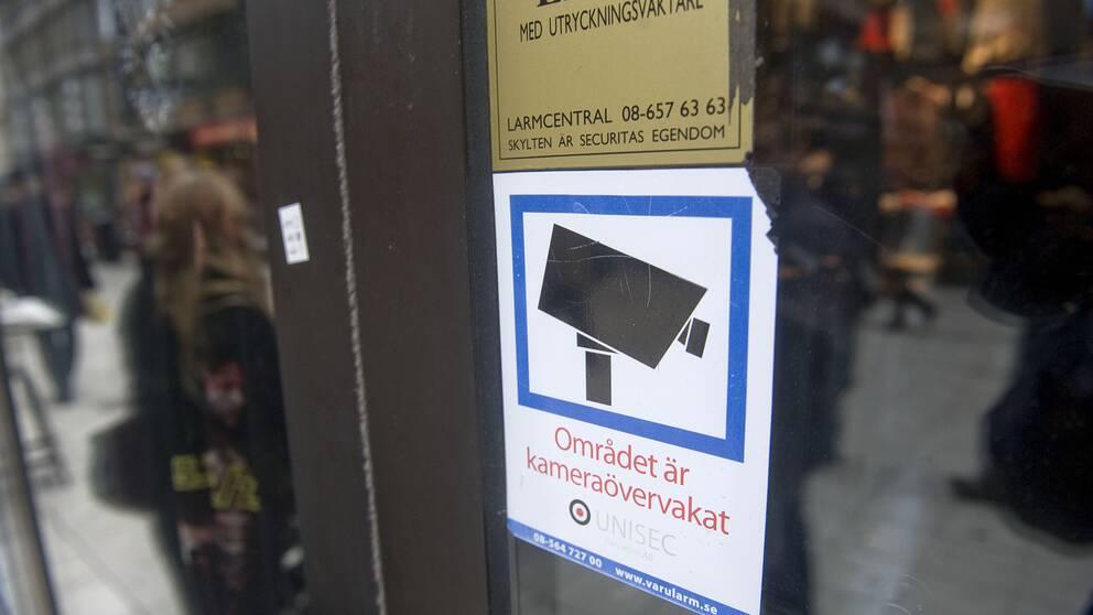 En bild på en skylt som visar övervakning utanför en matbutik.