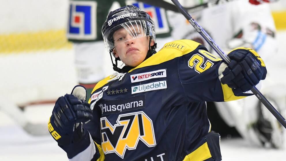 Man ikklädd ishockeymundering. HV71 tröja och ishockeyklubba.