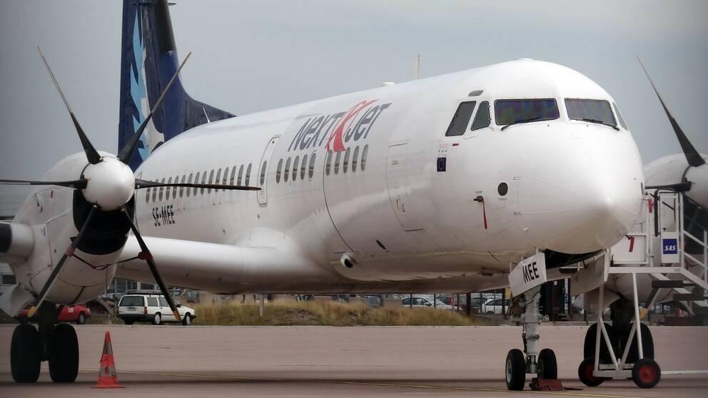 Ett flygplan parkerad på en flygplats av märket Nextjet