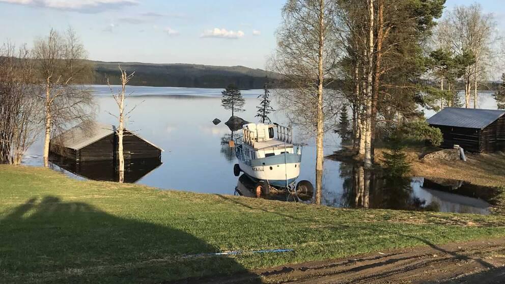 vy över grässlänt ner mot översvämmad sjö, lada i vatten, båt på vagn