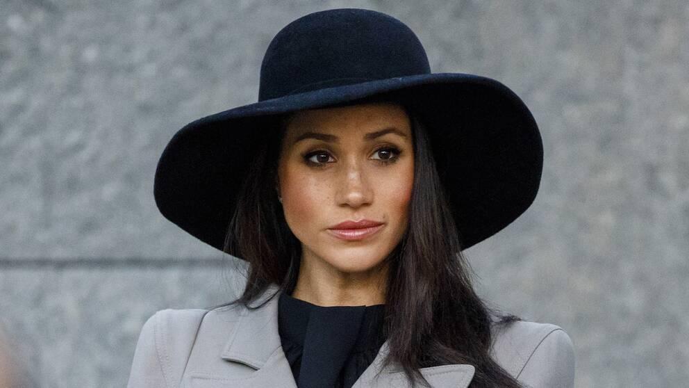 Meghan Markle i svart hatt ser allvarlig ut.