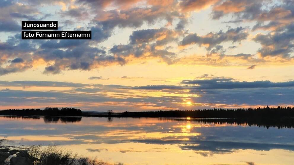 Måndagskväll och solen på väg ner över en spegelblank Torneälv i Junosuando Norrbotten. Mycket högt vattenflöde i älven även i norra Tornedalen.