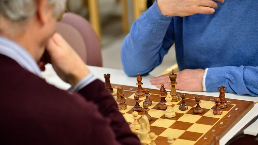 Två äldre män spelar schack