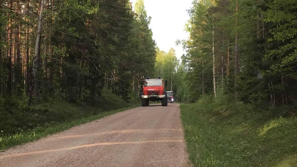 Räddningstjänsten åker på en skogsväg.