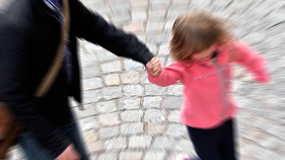 Vuxen som håller ett barn i handen. Suddig bild