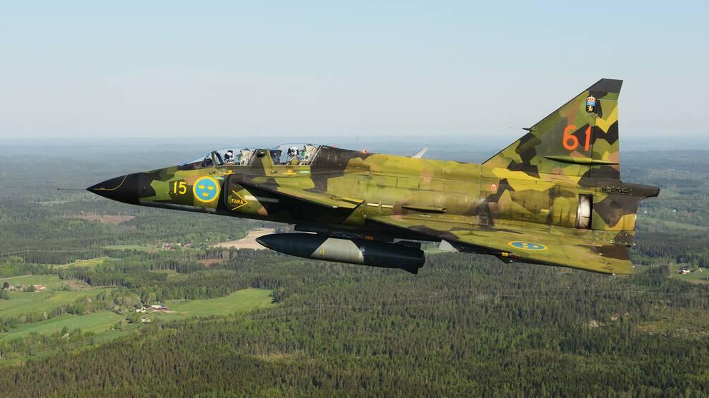 Grönmålat stridsflygplan i luften