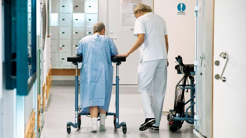 En patient med rullator går i sjukhuskorridoren tillsammans med personal.