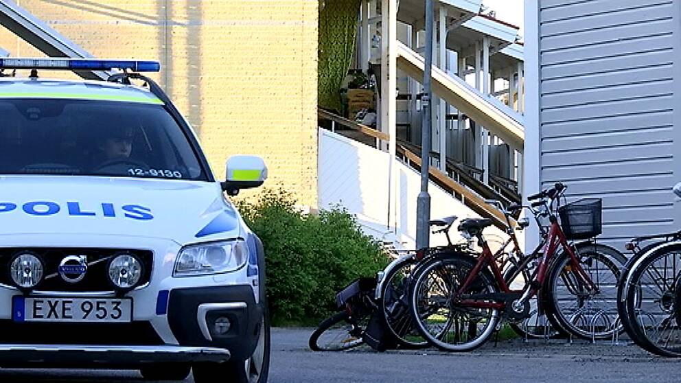 polisbil med polis i, står still utanför bostadsområde