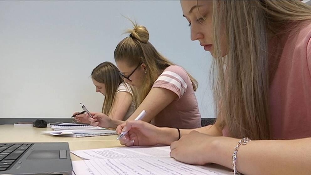 Tre tjejer sitter på rad i ett klassrum och pluggar, antecknar