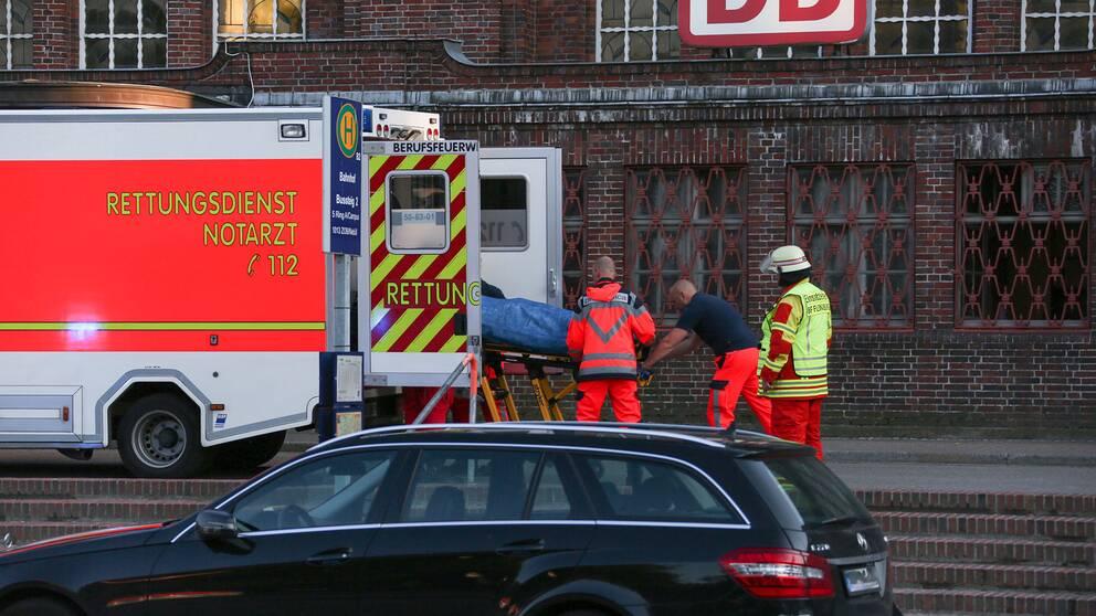 En person lastas i ambulans utanför tågstationen i Flensburg efter en knivattack på ett tåg.