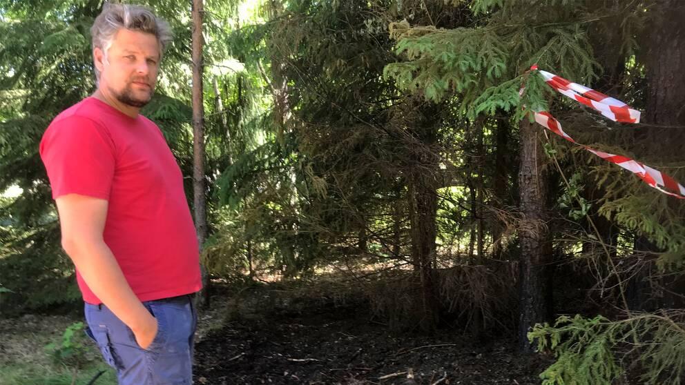 Man i röd t-shirt står i skog vid avspärrning (där det har brunnit).