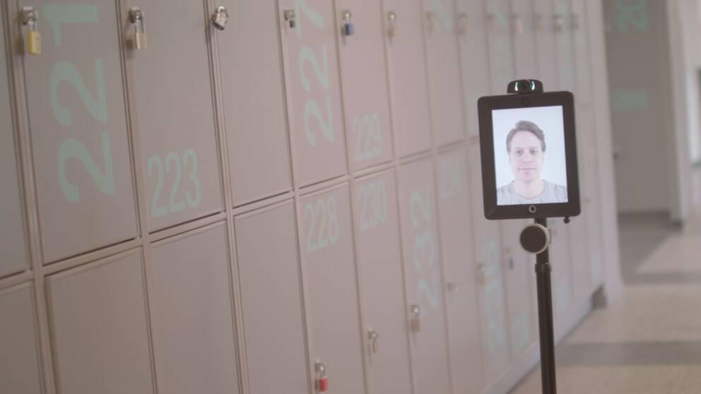 Lärare syns i en läsplatta som står på ett stativ i skolkorridor.