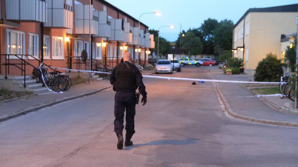 Polis går mot område som polisen spärrat av med tejp.