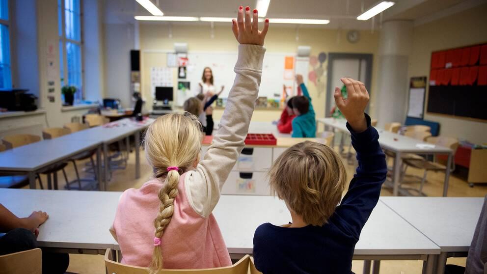 Elever räcker upp handen i klassrum