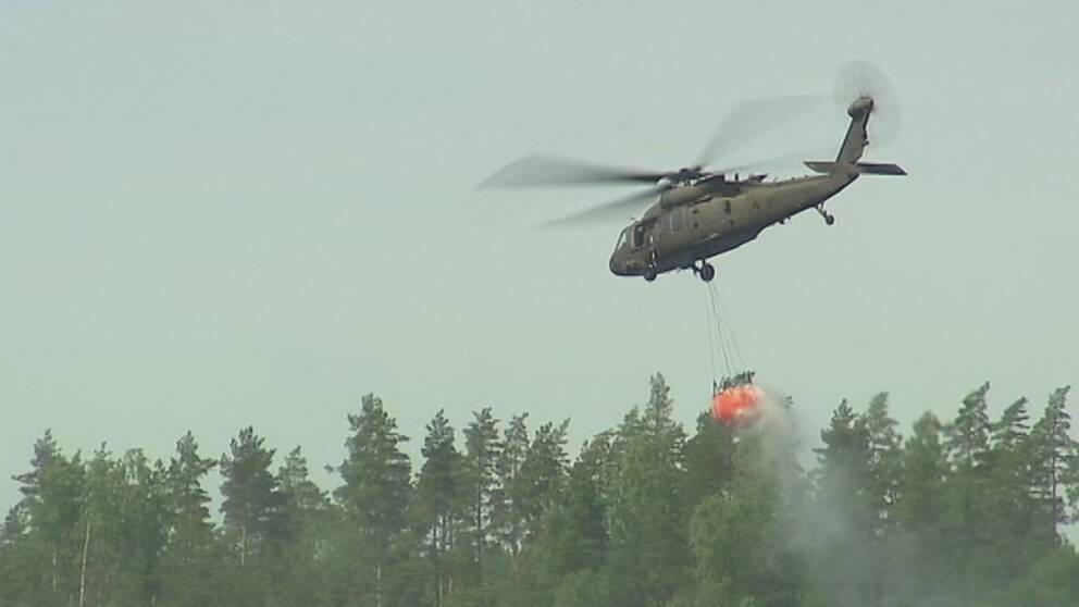 Helikopter flyger över skogen med vattenbehållare under.