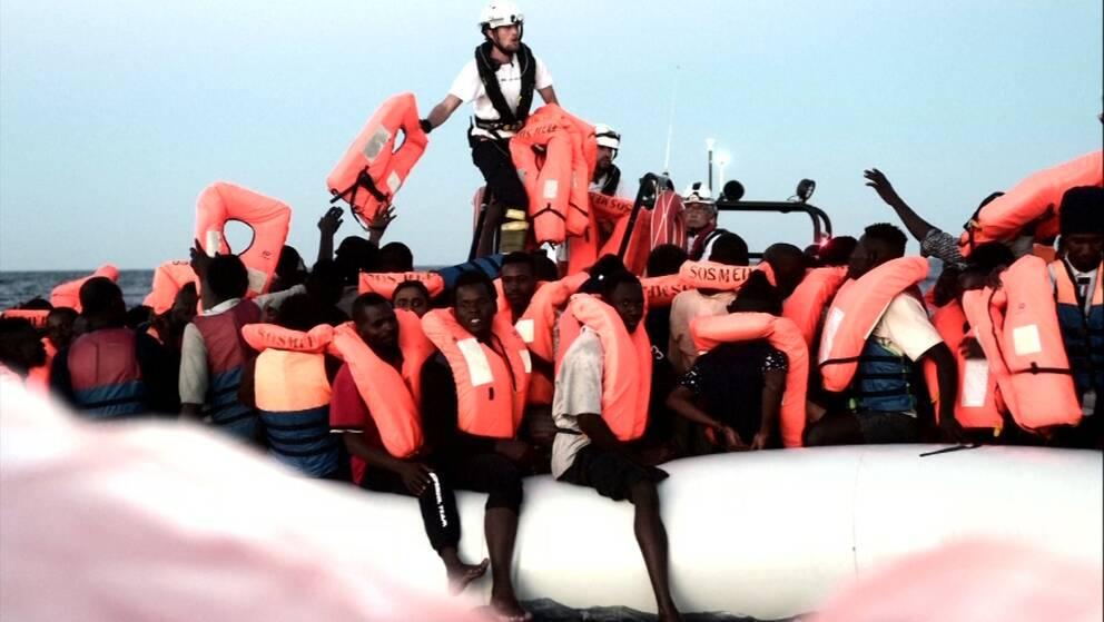 Flera personer i flytväst ombord en vit gummibåt ute till havs.