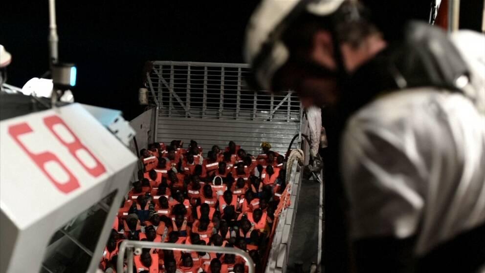 Migranter sitter ned i en båt som befinner sig på Medelhavet.