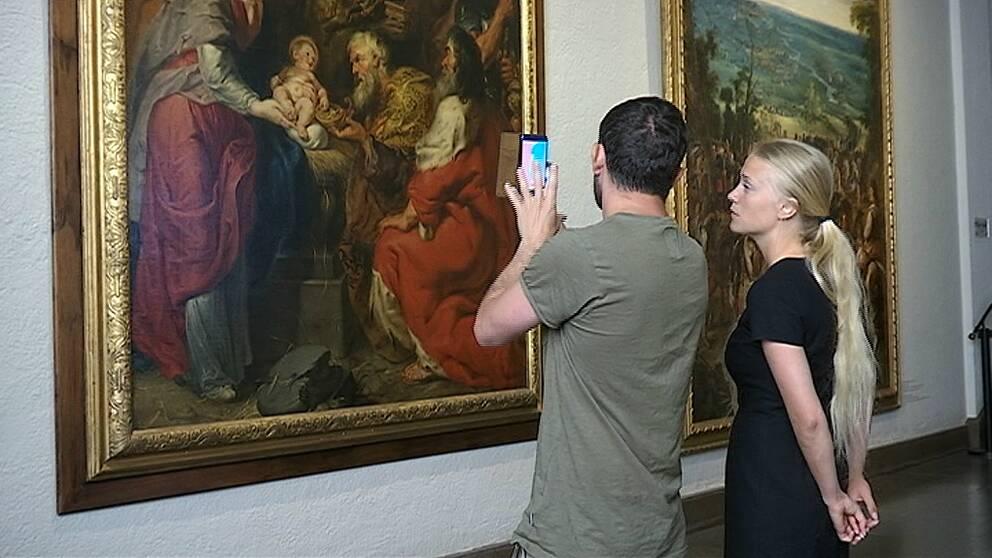 En bild på Johan Eijerblom som visar appen för reporter Lovisa Herold.