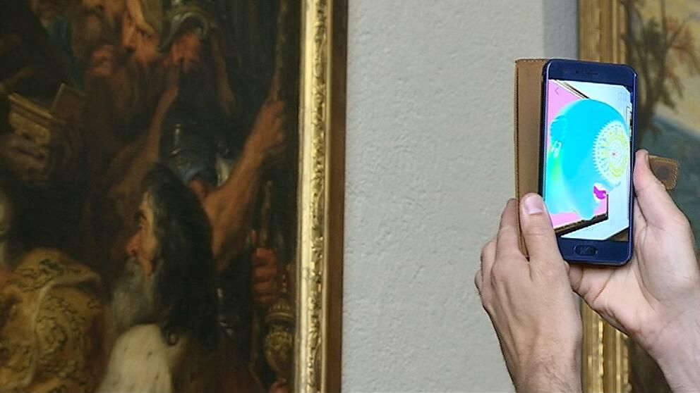 En bild på appen som filmar en målning. I telefonen syns en 3D-skulptur av ett ansikte.