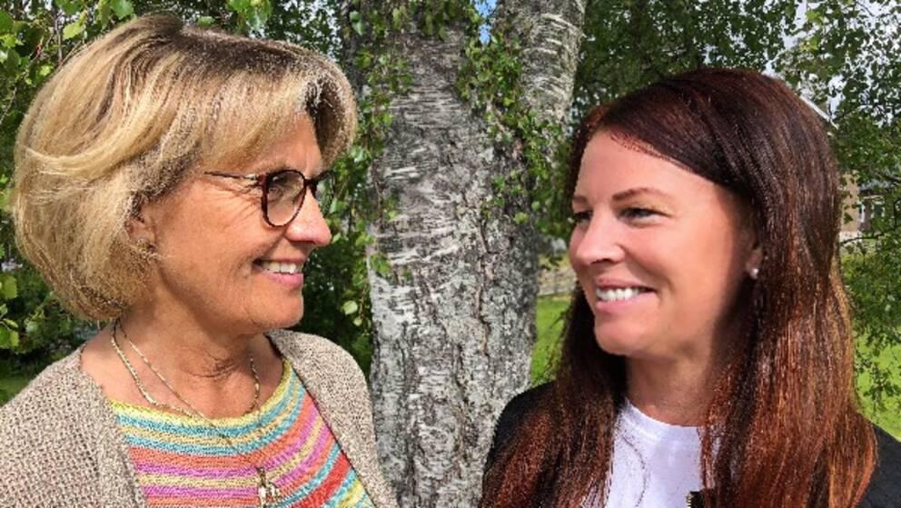 två leende kvinnor framför en björkstam