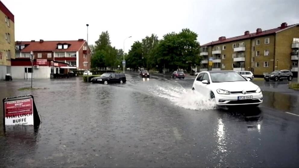 En bil som kör genom på en vattendränkt väg.
