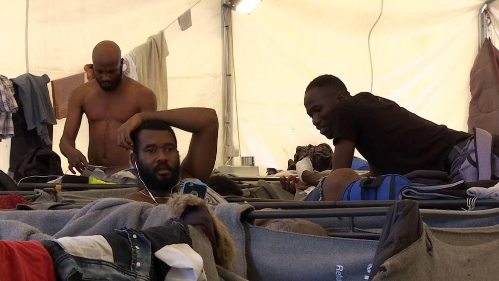 Flyktingar inne i ett tält. Kläder upphängda på linor.