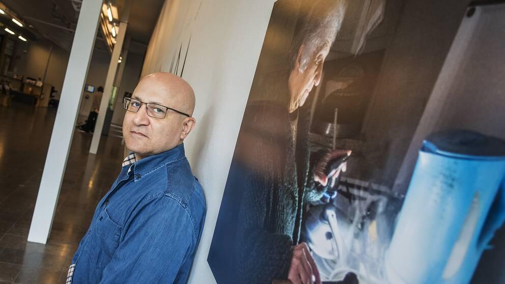 en man står vid en vägg med uppförstorat foto