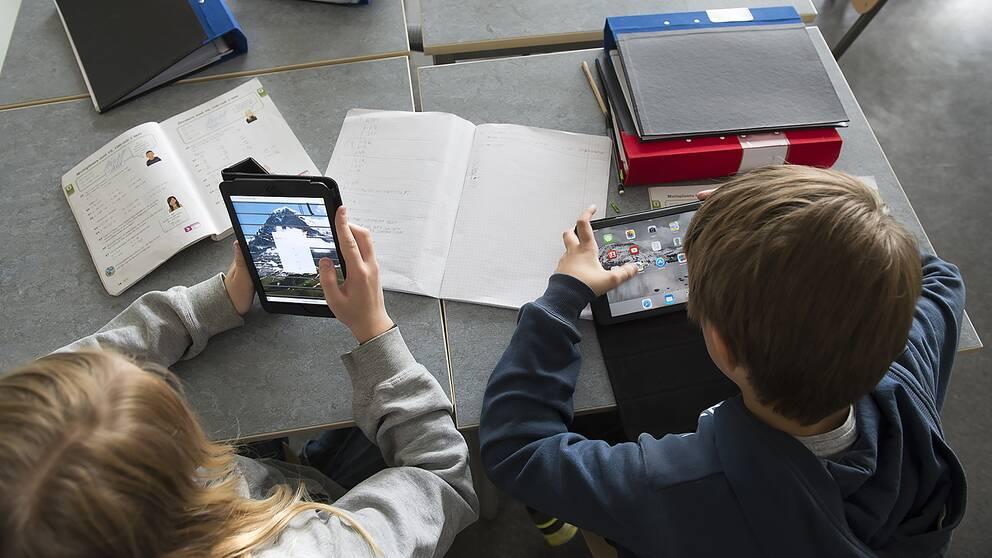 Skolelever med böcker och surfplattor