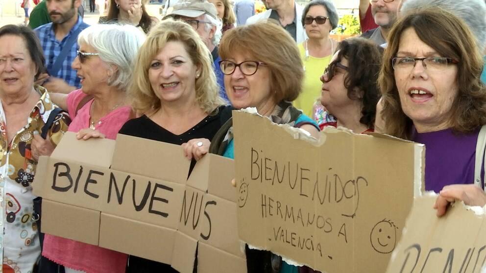"""I Valencias hamn har folk samlats för att ta emot fartyget Aquarius. En grupp kvinnor tillverkar skyltar där det står """"Välkomna!""""."""