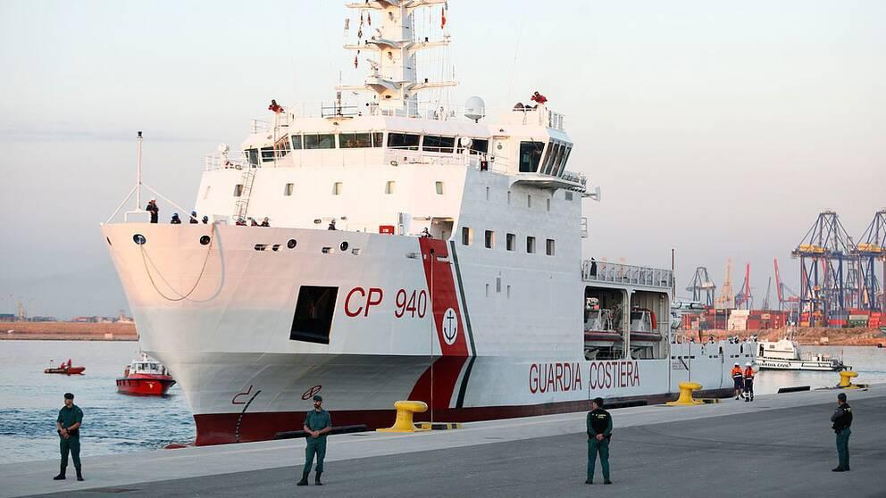 Kustvaktsbåten Dattilo i hamnen. Vakter står på land framför fartyget.