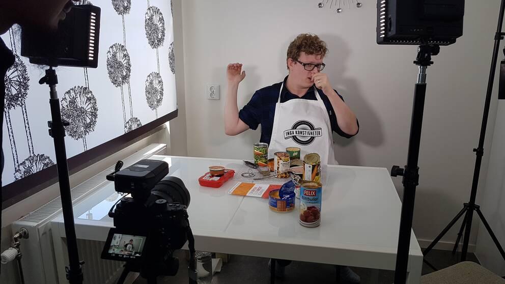 Youtubern Figgehn sitter vid ett bord med olika konserver framför sig.
