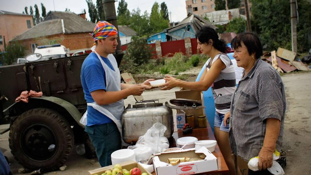 En hjälparbetare delar ut mat och vatten till invånare som drabbats av översvämningen i staden Krymsk.