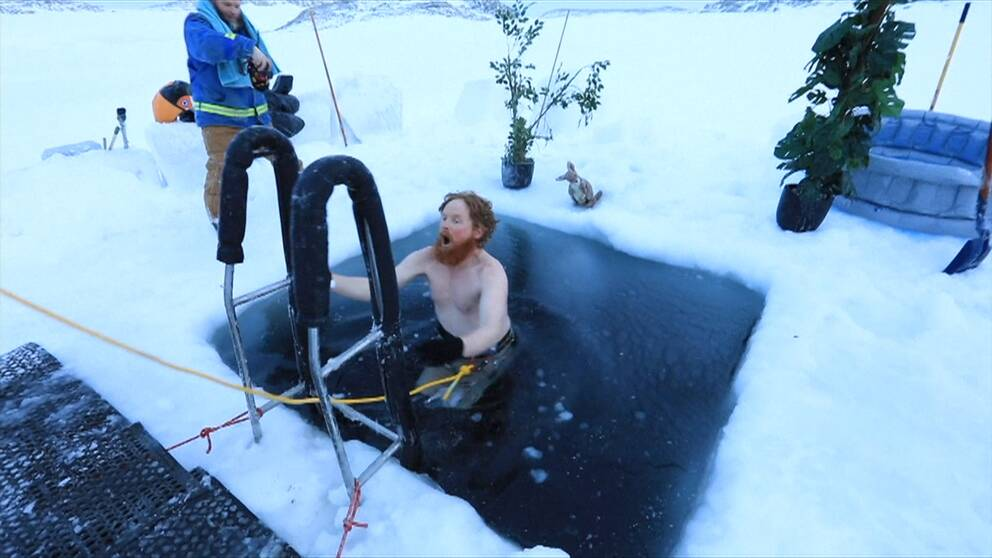Man kliver ned för stege till öppet vatten i en isvak.
