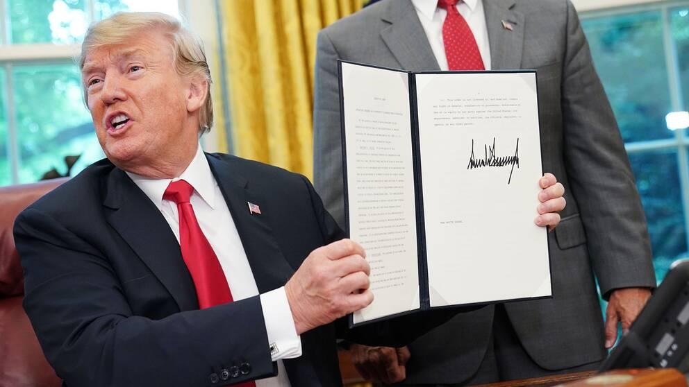 Donald Trump visar upp presidentordern som ska sätta stopp för att migrantfamiljer splittras vid gränsen till USA.